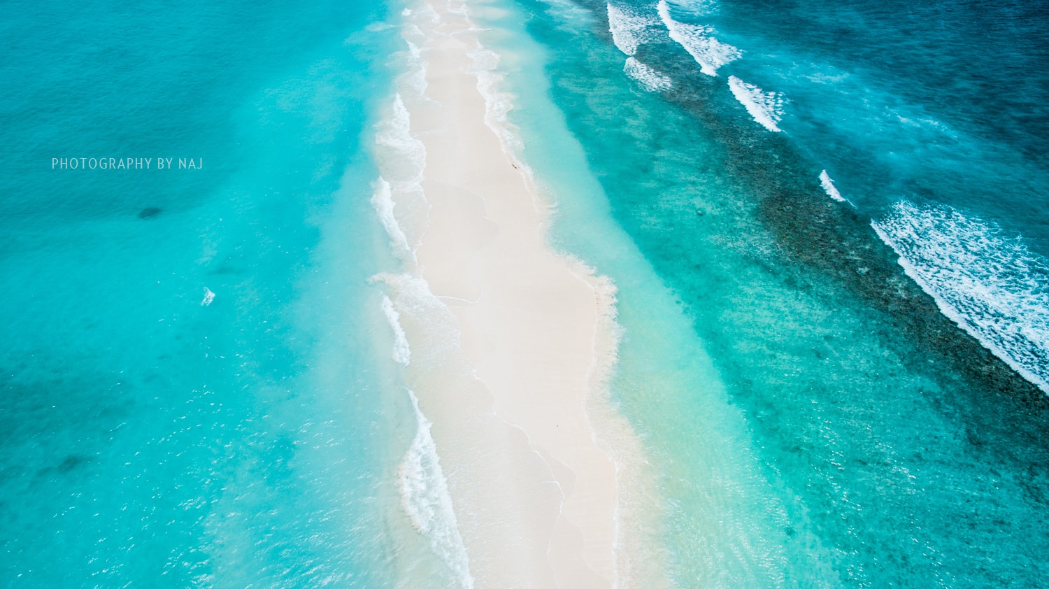 Sandbank lapped on both sides by the turquoise Indian Ocean in the Maldives
